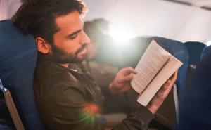 Чтение книги в полете на самолете